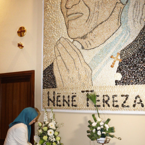 Offering flowers to the portrait of Mother Theresa at Saint Paul Cathedral, Tirana