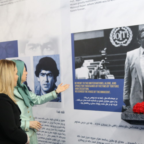Maryam Rajavi and Mrs. Monika Kryemadhi standing before the portrait of Prof. Kazem Rajavi in the Exhibition of 120 Years of Iranian People's Struggle for Freedom