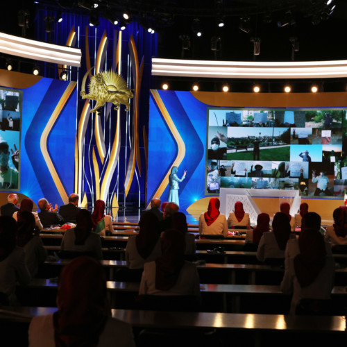 Maryam Rajavi at the Free Iran Global Summit standing in front of collage of Resistance Units in Iran – Ashraf 3, July 17, 2020.